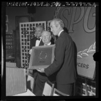 Director Alfred Hitchcock receiving Producers Guild award from actors James Stewart and Cary Grant, 1965