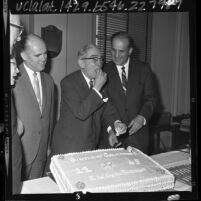 Los Angeles County Sheriff Pete Pitchess watches retired sheriff Eugene Biscailuz sample his 82nd birthday cake, 1965