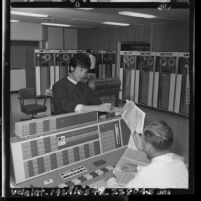 Gemini flight engineer Annette Chambers conferring with co-worker in data processing center om El Segundo, Calif., 1965