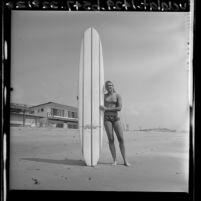 Women's world surfing champion Joyce Hoffman standing with longboard in San Juan Capistrano, Calif., 1964
