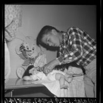 5th grade boy pinning diaper on baby doll in family life class at Steele Elementary School, Torrance, Calif., 1965