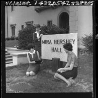 Three female UCLA students gathered around Mira Hershey Hall sign, 1965