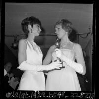 "Actress Audrey Hepburn handing Julie Andrews her best actress Oscar for film ""Mary Poppins,"" 1965"