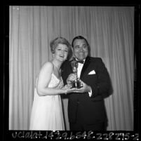 Comedian Jonathan Winters and actress Angela Lansbury posing with an Oscar at the 1965 Academy Awards