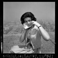 Jo Jeanne Angeloff rubbing eyes from effects of smog atop the Occidental Center building in Los Angeles, Calif., 1965