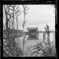 Man fishing from Tiki house on one acre lake in the desert community of Newberry Springs, Calif., 1965