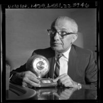 Fred G. Burg of Burgmaster Corp. displaying clock he invented that gives time for 166 cities around the world, 1965