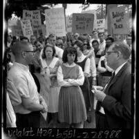 Whittier College president Paul S. Smith talking with student leader Dean Pitts in front of group of student demonstrators, Calif., 1965