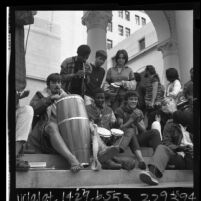 "Group of ""Venice bohemians"" playing bongos on steps of Los Angeles City Hall to protest city ordinance, 1965"