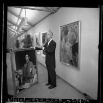 Artist Norman Rockwell standing amongst his paintings at exhibit at Municipal Art Gallery at Barnsdall Park, Los Angeles, 1965