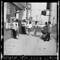 Teenagers hanging out on street corner because of closure of anti-poverty Summer Teen Program  in Wilmington, Calif. , 1965