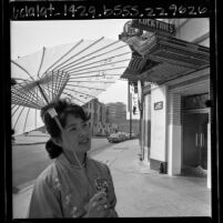 Takako Hoshiba with parasol walking down street during Los Angeles' Little Tokyo renewal efforts, 1965