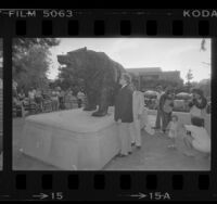 """Chancellor Charles E. Young and others viewing """"The Bruin Bear"""" sculpture on UCLA campus, 1984"""