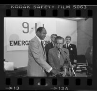 "Los Angeles Mayor Tom Bradley and Councilman Marvin Braude flipping ""on switch"" for 911 emergency telephone system, 1984"