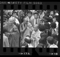 Tenzin Gyatso, Dalai Lama XIV surrounded by people during visit to Vietnamese Temple in Los Angeles, Calif., 1984