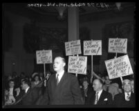 Attorney Gregory Creutz speaking before Board of Supervisors as people behind him hold up signs protesting oil drilling in Los Angeles, Calif., 1947