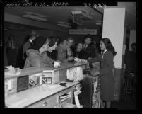 Actors Marsha Hunt, Humphrey Bogart, Lauren Bacall and others at airport ticket counter on way to Washington D.C. to see Un-American Activities Committee