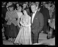 Actors Natalie Wood and Tab Hunter arriving at the 28th Academy Awards with gossip writer Louella Parsons in background, 1956