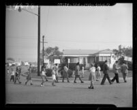 Labor union members picketing home of glass manufacturer Samuel Moss as neighborhood children picket them in Los Angeles, Calif., 1947