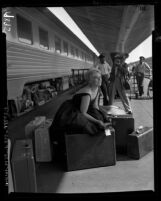 Actress Kim Novak posing for reporters on the train platform at Los Angeles Union Station, 1956