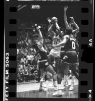 UCLA basketball player, Reggie Miller driving to the net as Washington State players try to block during game in 1985