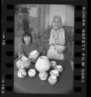 Writer and potter Susan Peterson with American Indian potter Lucy Lewis displaying Lewis' work in Los Angeles, Calif., 1984