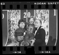 Doug Flutie and Bob Hope carrying gymnast Mary Lou Retton during taping of Bob Hope's Christmas television show, 1984
