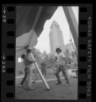 Workers setting up tent for the homeless Tent City, across the street from City Hall in Los Angeles, Calif., 1984