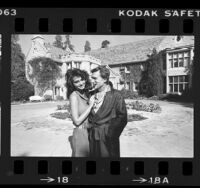 Publisher Hugh Hefner in trademark pajamas with Carrie Leigh in front of Playboy Mansion in Los Angeles, Calif., 1984