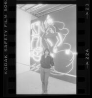 "Neon Artist Lili Lakich standing with her work ""Love in Vain"" in Los Angeles, Calif., 1984"