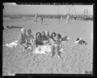 Eight girls lying in the sand while tanning  with jetty in the background at Cabrillo Beach, Calif., 1947