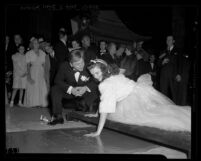 "Mickey Rooney watching Judy Garland put handprint in cement at Grauman's Theatre during ""Babes in Arms"" film premiere, Hollywood (Los Angeles), 1939"