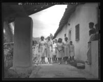 Girls in white veils, on their way to Pala mission chapel to join in the religious procession, Calif., 1938