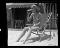 Actress Jane Wyman sitting in lounge chair on California beach, 1935