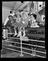 Comedians George Burns and Gracie Allen and children standing at rail of ship in Los Angeles, Calif., 1938