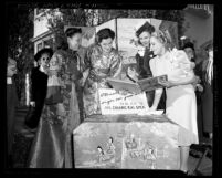Actresses Rosalind Russell, Jane Withers and Mary Pickford signing guest register at Chinese War Orphans charity event in Los Angeles, Calif., 1940