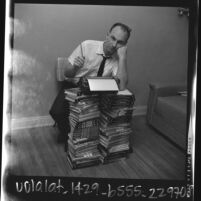 Writer Vernon Howard leaning against stacks of his self improvement books