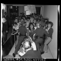 Two police officers holding back a group of Sonny and Cher fans at Los Angeles International Airport, 1965
