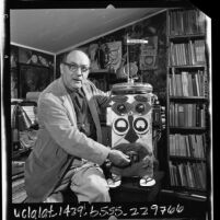 Author Lawrence Lipton, chronicler of the beatnik scene, demonstrating his robot, DUHAB