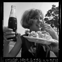 Young woman eating diet cola and french fries in Los Angeles, Calif., 1965