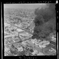 Aerial view of two buildings on fire on Avalon Blvd. between 107th and 108th street during Watts Riots, Los Angeles, 1965