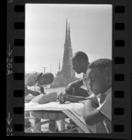 Against the background of the Watts Towers, art instructor Judson Powell with two students 1965