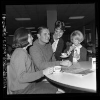UCLA football player Kurt Altenberg taking a break with three coeds in UCLA Student Union, 1965