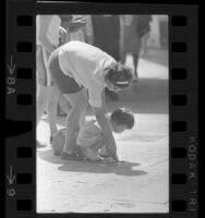 Woman and little girl examining hand imprints at Grauman's Chinese Theater, Hollywood (Los Angeles), 1965