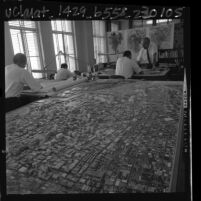 Men working at drafting tables next to scale model of Los Angeles in Los Angeles City Planning Department, 1965