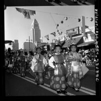 Children from Los Angeles Buddhist Federation in traditional dress walking in Los Angeles Nisei Week parade, 1965
