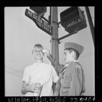 Boy Scout wiping the eyes of girl during smog alert in Reseda, Calif., 1965