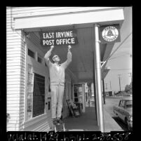 Postmaster William A. Cook hanging sign designating building as East Irvine post office, Irvine, Calif., 1965