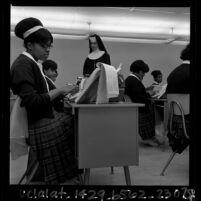 African American nun instructing girls in typing class at Regina Caeli High School in Compton, Calif., 1965