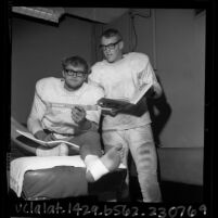 Two California Institute of Technology football players in uniforms studying physics, 1965